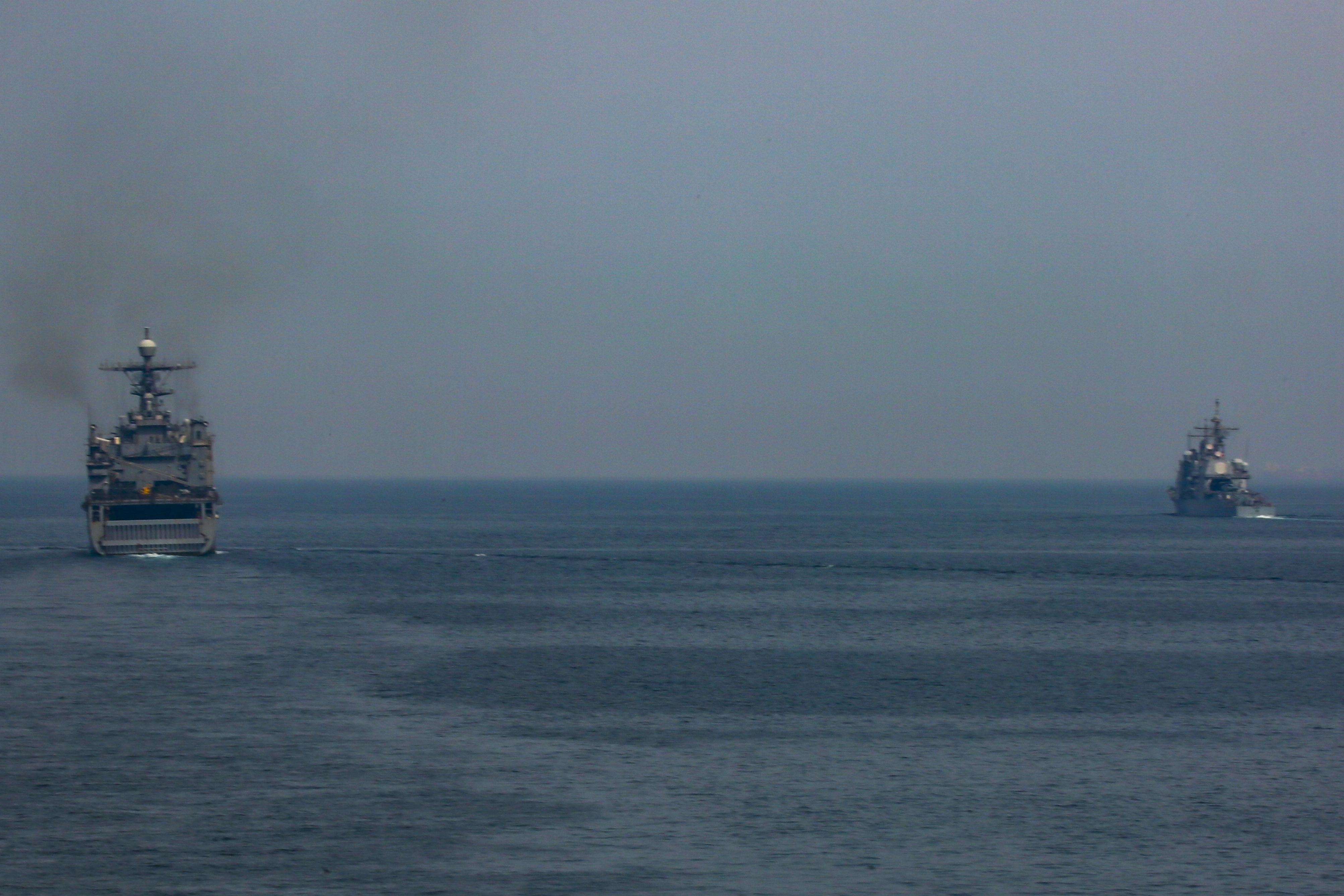 USS Oak Hill (LSD 51), left, and guided-missile cruiser USS Vella Gulf (CG 72) transit the Strait of Hormuz